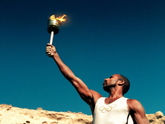 olympic-torch-flame-runner-hold-sky-modern-olympic-logo-t-shirt-african-olympian-photo